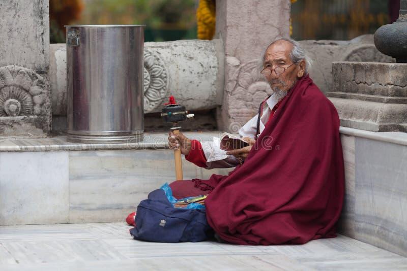 Le vieux pèlerin bouddhiste, tourne une petite roue image libre de droits