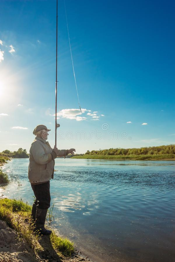 Le vieux pêcheur sur la rivière le soir image stock