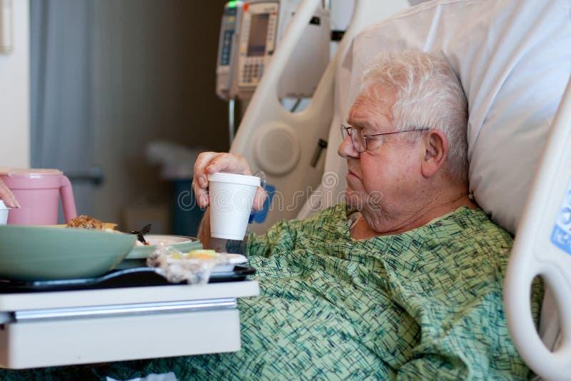 Le vieux patient hospitalisé mâle boit l'eau photo libre de droits