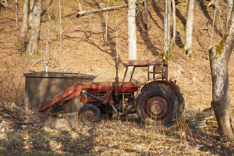 Le vieux tracteur rouge a abandonné dans une forêt photo stock