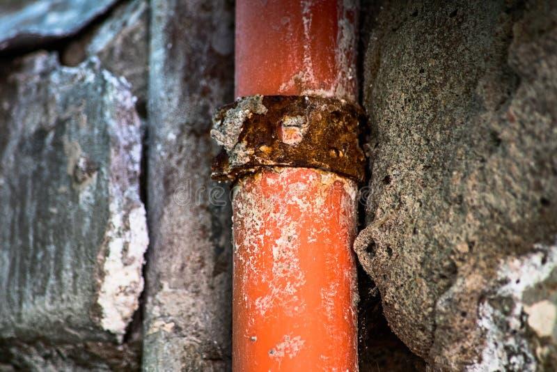 Le vieux tuyau rouillé dans le mur ruiné de la maison photo libre de droits