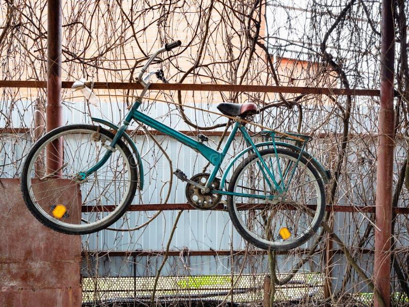 Le vieux vélo accroche sur la barrière du hangar de village photographie stock libre de droits
