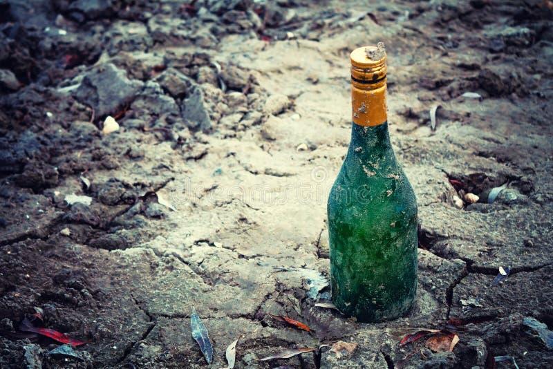 Le vieux vert de bouteille de vin se trouve sur le bord de mer dans le sable image libre de droits