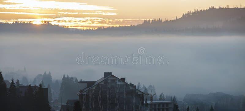 Le village de station de vacances loge des bâtiments sur le fond des collines bleues brumeuses de montagne couvertes de forêt imp photo stock