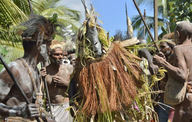 Le village suit les ancêtres incorporés dans le masque d'esprit pendant qu'ils voyagent le village image stock