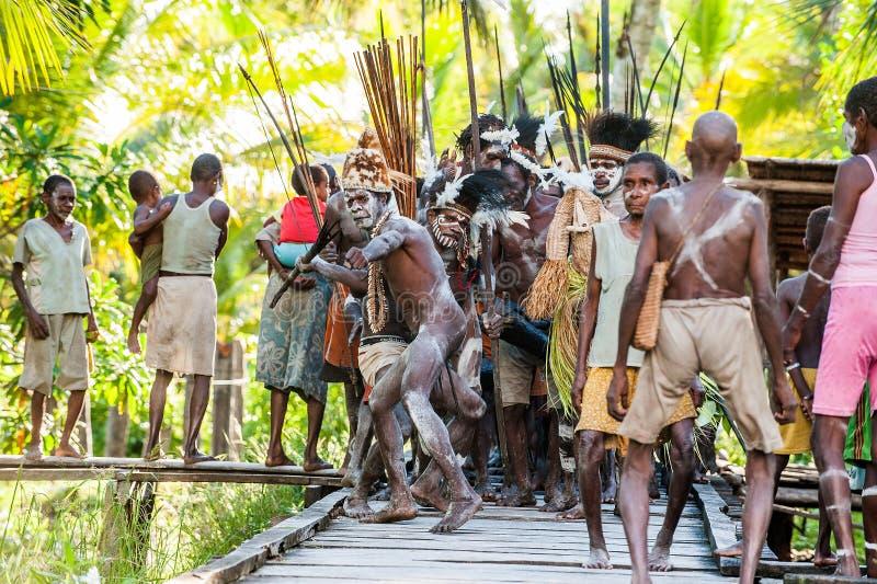 Le village suit les ancêtres incorporés dans le masque d'esprit pendant qu'ils voyagent le village la cérémonie de Doroe image stock