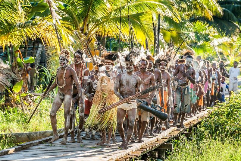Le village suit les ancêtres incorporés dans le masque d'esprit pendant qu'ils voyagent le village la cérémonie de Doroe photos libres de droits