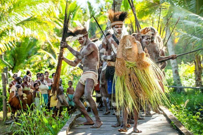 Le village suit les ancêtres incorporés dans le masque d'esprit pendant qu'ils voyagent le village la cérémonie de Doroe photos stock