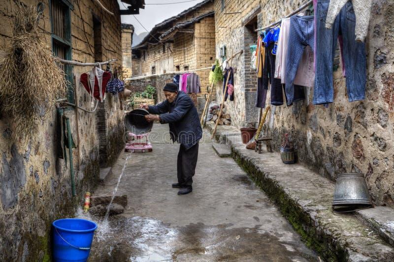 Le villageois plus âgé asiatique verse l'eau du seau sur la rue étroite image stock