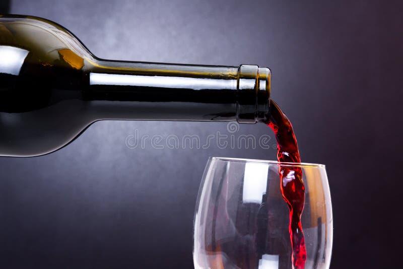 Le vin rouge verse dans le plan rapproché en verre Vin versant pour nettoyer le verre photographie stock libre de droits