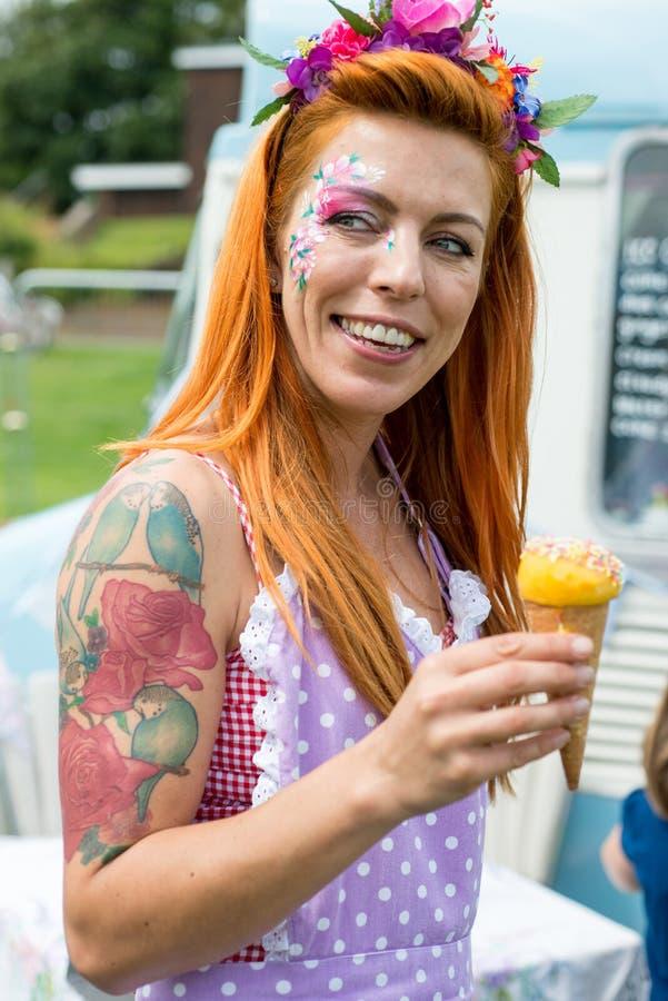 Le vintage de port de sourire de dame d'une chevelure rouge habillent tenir la crème glacée  image libre de droits