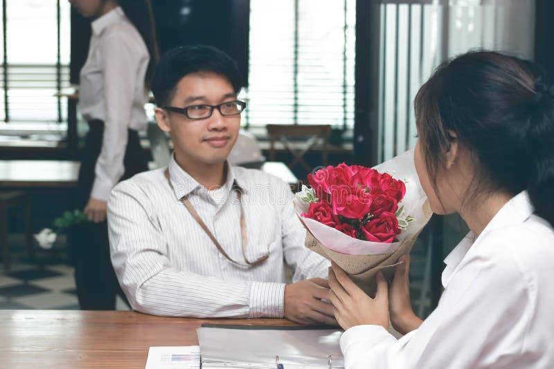 Le vintage a modifié la tonalité l'image de la jeune femme asiatique gaie acceptant un bouquet des roses rouges de l'ami avec le  images stock