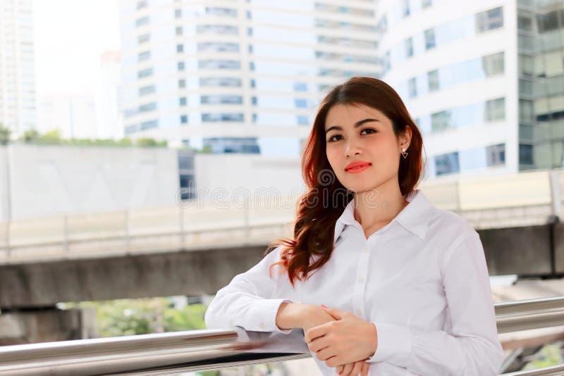 Le vintage a modifié la tonalité l'image de la jeune femme asiatique sûre avec la chemise blanche au fond urbain de public de bât photo libre de droits