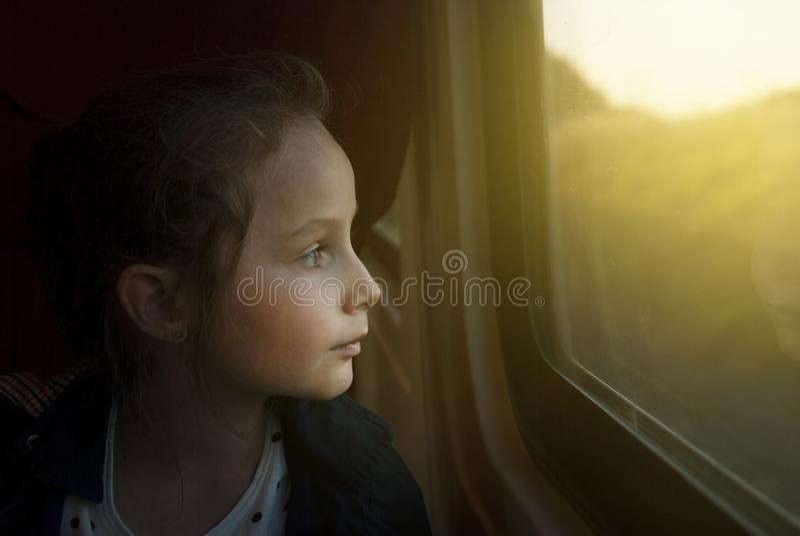 Le vintage a modifié la tonalité le mage de la petite fille regardant par la fenêtre Elle voyage sur un train ferroviaire Copiez  photographie stock