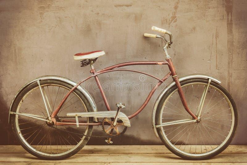 Le vintage s'est rouillé bicyclette de croiseur sur un plancher en bois photographie stock libre de droits
