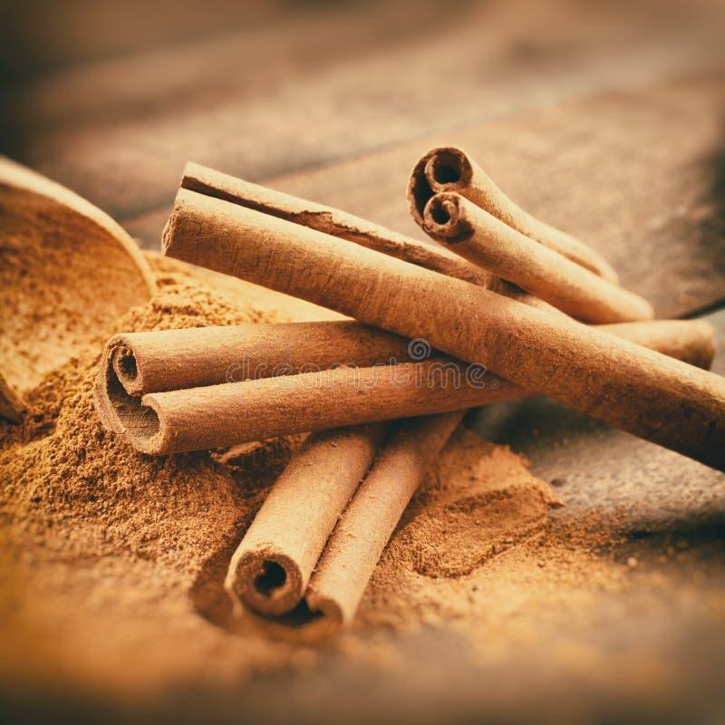 Le vintage a stylisé la photo des bâtons de cannelle et de la poudre de cannelle photos libres de droits