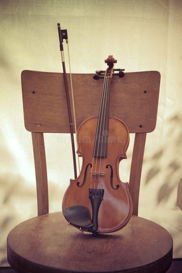 le violon et l'arc, se tiennent sur une vieille chaise en bois Art de concept Le style de vintage a modifi? la tonalit? la photo images stock