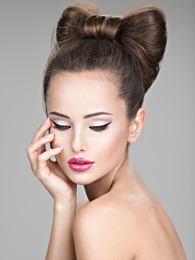 Le visage d'une belle femme avec un maquillage de couleurs vives photo libre de droits
