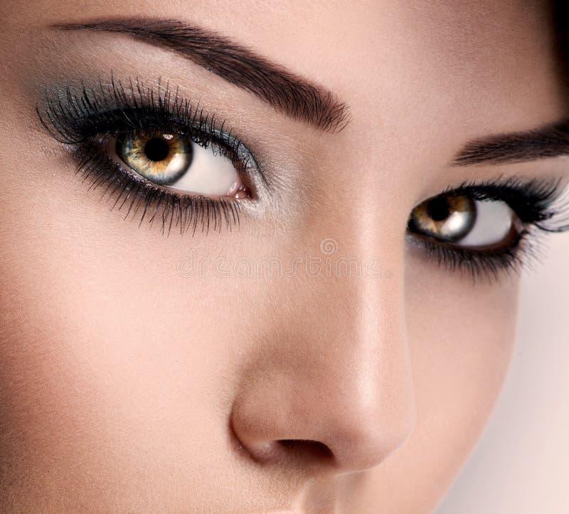 Le visage de la femme aux beaux yeux bleus avec de longs cils photo stock