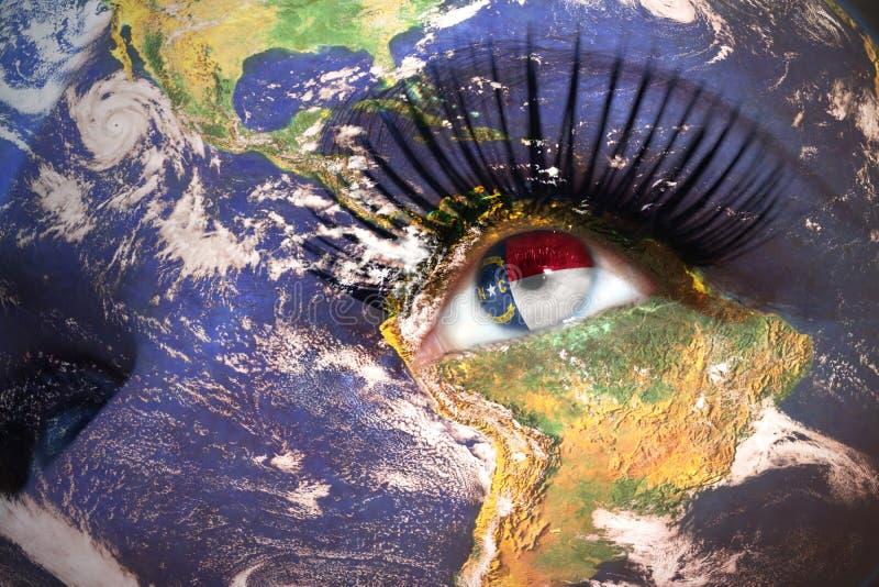 Le visage de la femme avec la texture de la terre de planète et la Caroline du Nord énoncent le drapeau à l'intérieur de l'oeil images stock