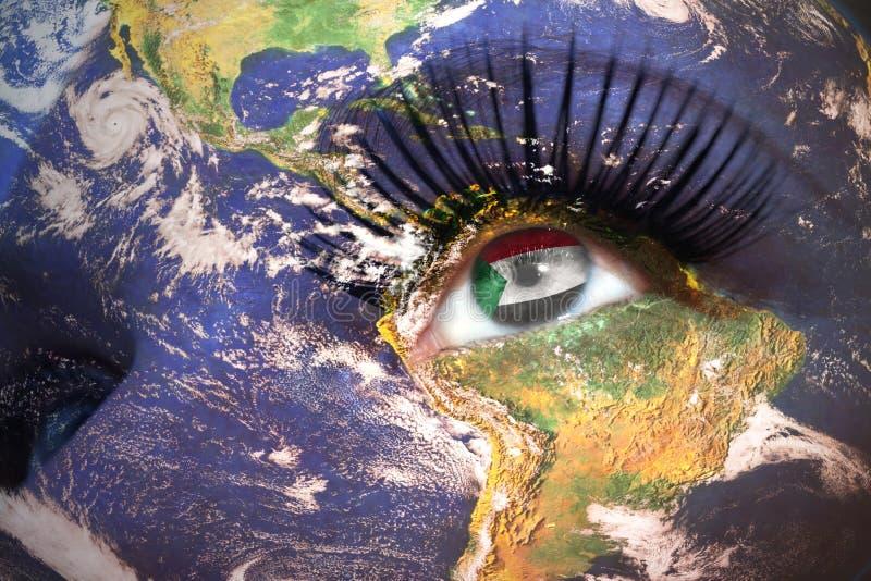 Le visage de la femme avec la texture de la terre de planète et le drapeau soudanais à l'intérieur de l'oeil photographie stock
