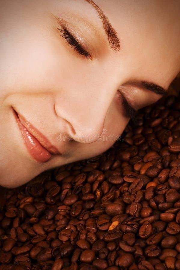 Le visage de la fille au-dessus des grains de café photographie stock