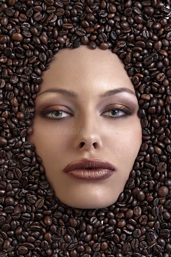 Le visage de la jolie fille immergé dans des grains de café photo stock