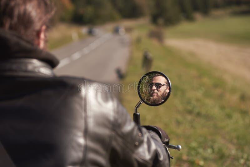Le visage de sourire du cycliste heureux barbu beau dans des lunettes de soleil foncées s'est reflété dans le miroir de motocycle photographie stock