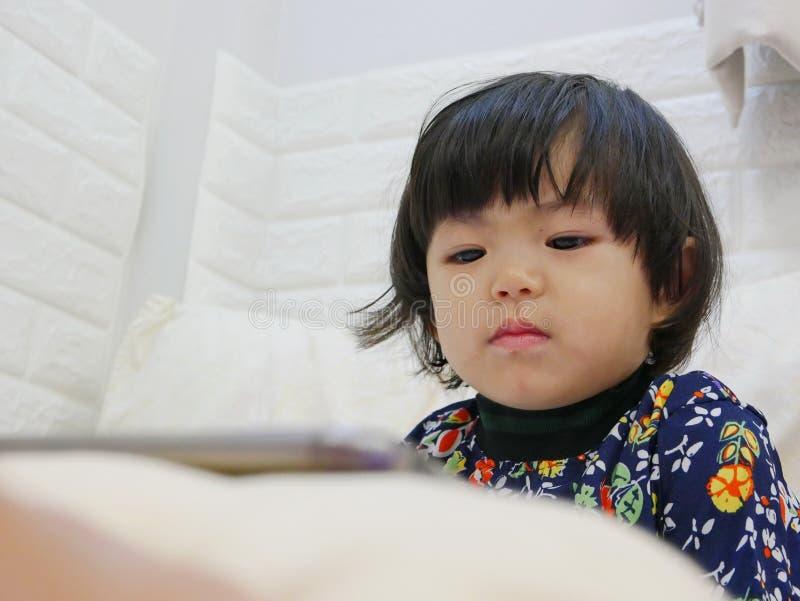 Le visage du petit bébé, 2 années, tout en observante/regardant fixement un smartphone photos libres de droits