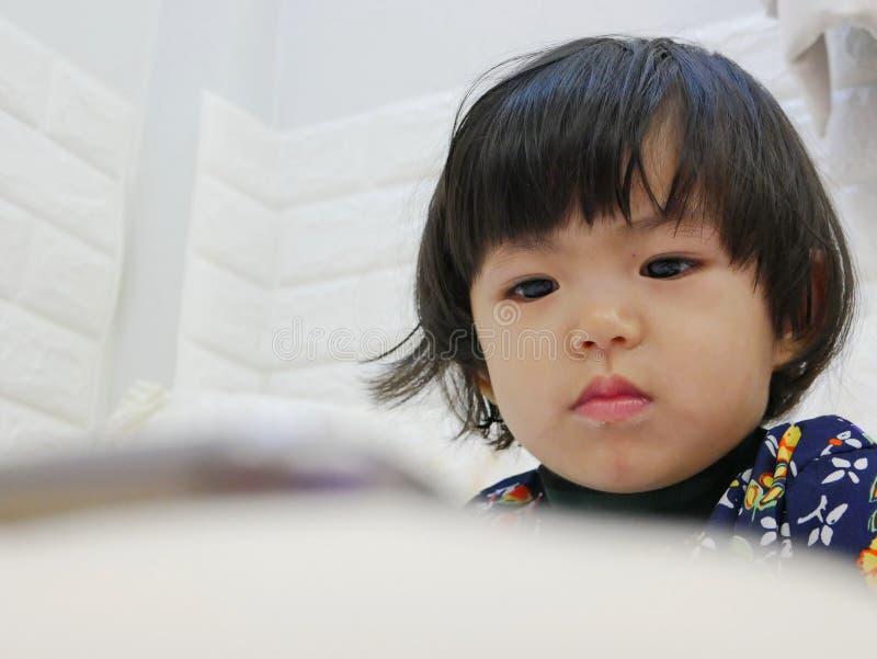 Le visage du petit bébé, 2 années, tout en observante/regardant fixement un smartphone photos stock