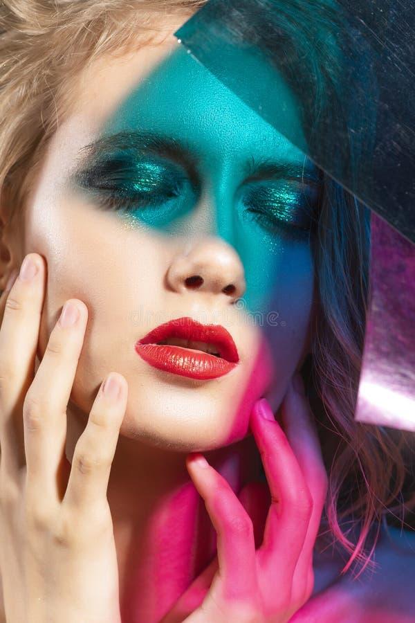 Le visage en gros plan d'une belle jeune fille blonde avec les lèvres rouges et son visage est couvert d'ombres colorées de mul images libres de droits