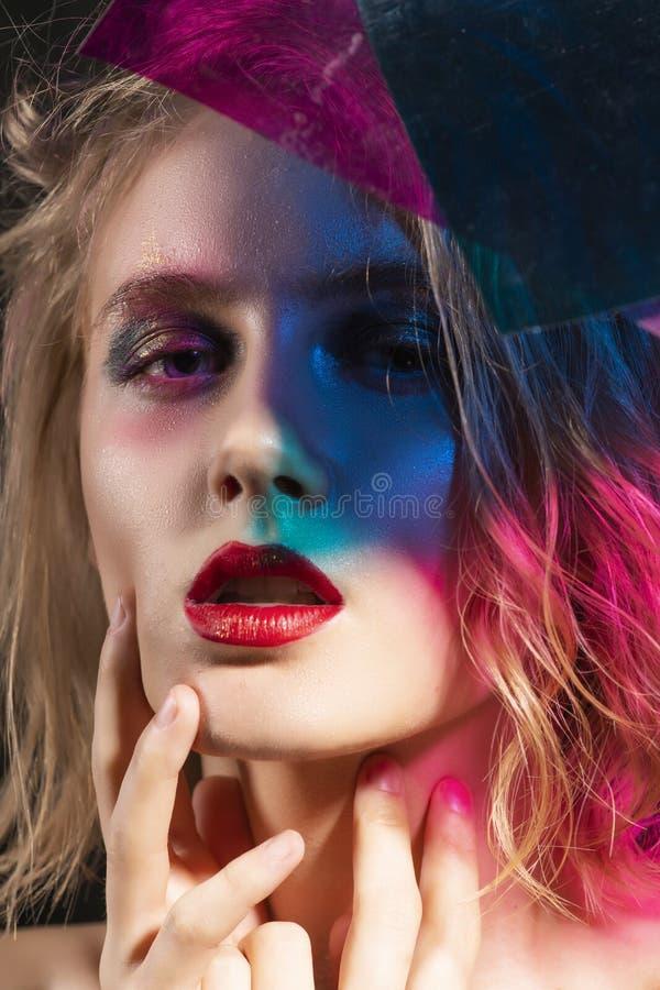 Le visage en gros plan d'une belle jeune fille blonde avec les lèvres rouges et son visage est couvert d'ombres colorées de mul photo stock