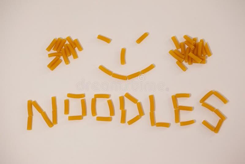 Le visage et les nouilles souriants textotent fait hors des pâtes de pennette photographie stock libre de droits