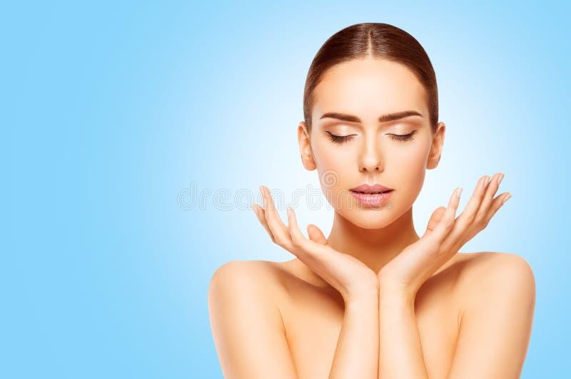 Le visage et les soins de la peau de beauté de mains, femme naturelle composent, modèlent sur le bleu photo stock