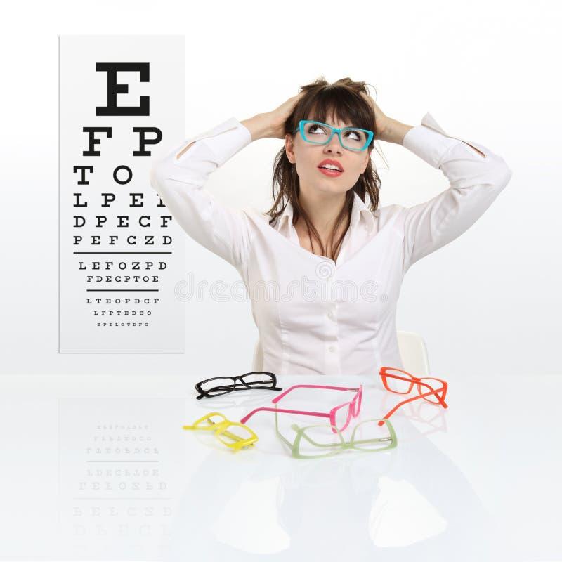 Le visage femelle de sourire choisit des lunettes sur le diagramme d'essai de vue photo stock
