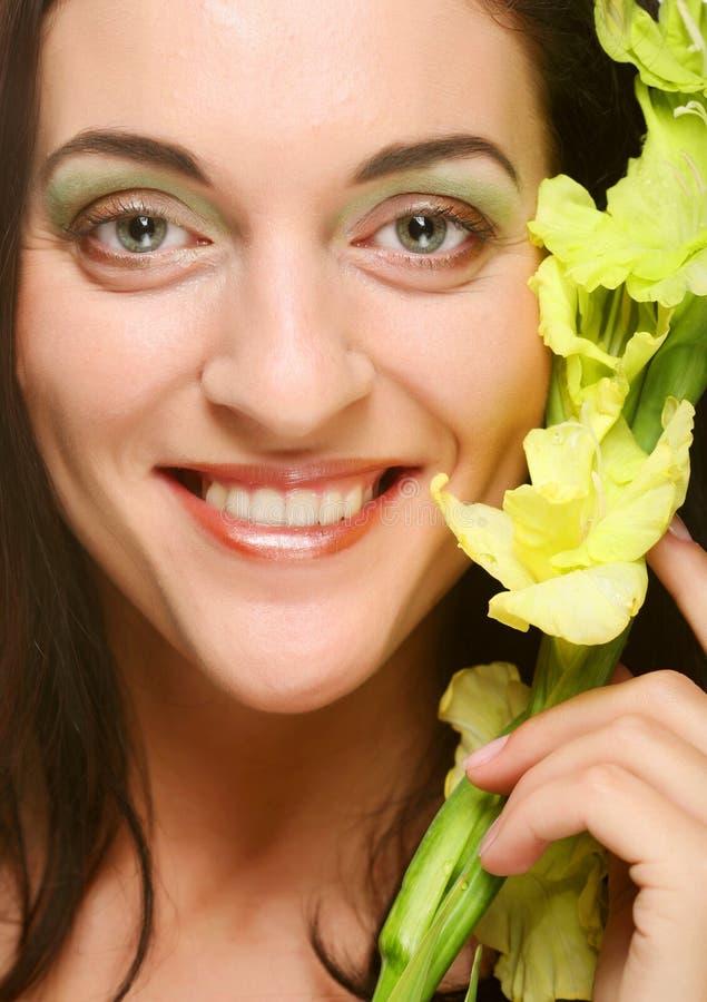 Le visage frais avec le gladiolus fleurit dans des ses mains image libre de droits