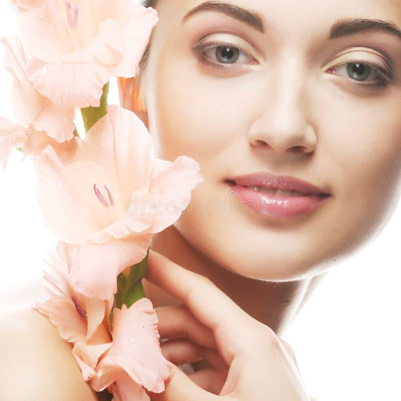 Le visage frais avec le gladiolus fleurit dans des ses mains photographie stock
