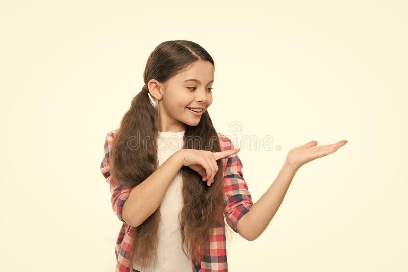 Le visage gai de sourire heureux d'enfant avec la coiffure adorable montrent quelque chose sur l'espace ouvert de copie de paume  image libre de droits