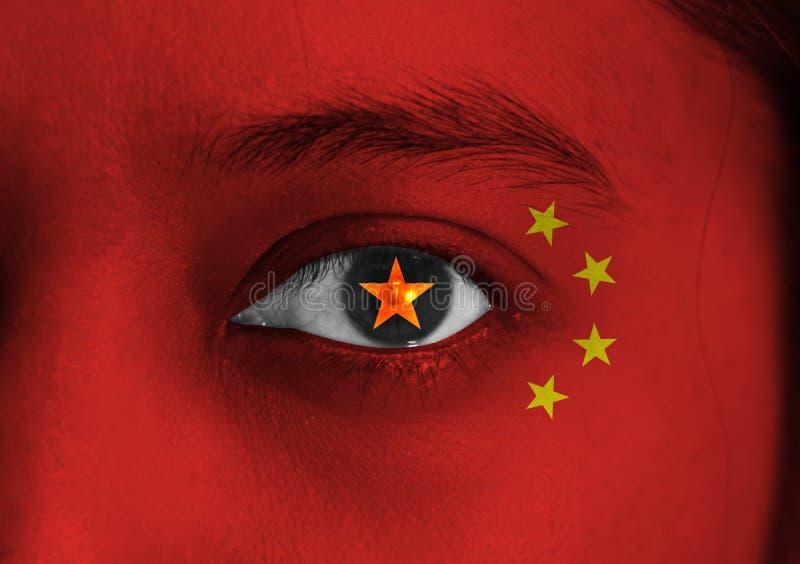 Le visage humain peint drapeau de la Chine avec une étoile jaune au centre de l'oeil ou du globe oculaire photo stock