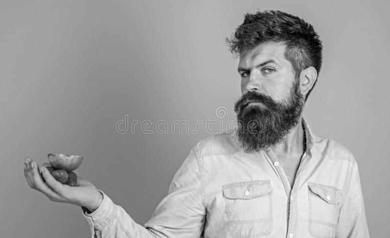 Le visage strict d'homme avec la barbe offre les festins organiques Je prends des festins pour vous Fraises et pomme barbues de p photographie stock libre de droits