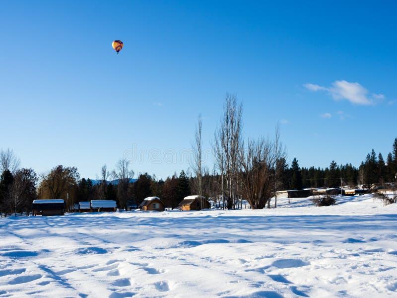 Le vol chaud coloré de ballon à air au-dessus d'une neige a couvert le champ photographie stock libre de droits