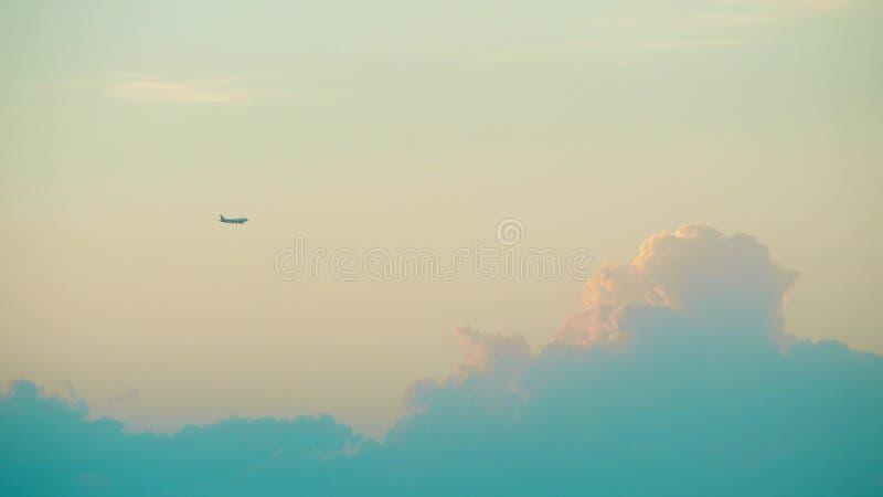 Le vol commercial éloigné d'avion contre le beau coucher du soleil opacifie photo stock