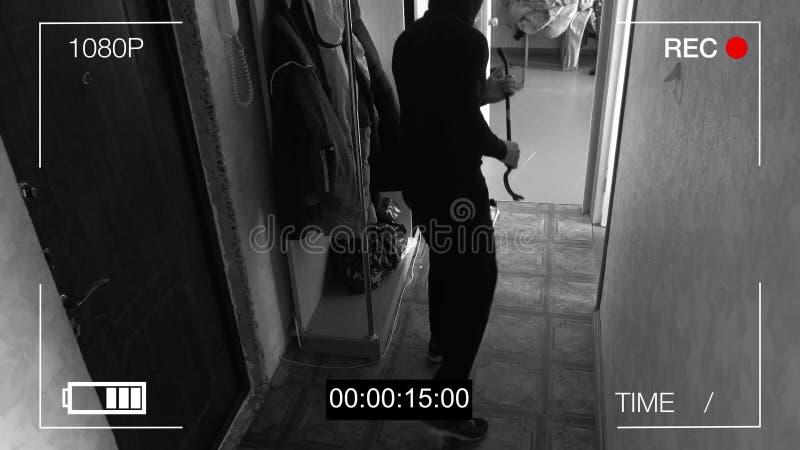 Le voleur attrapé par appareil-photo de télévision en circuit fermé avec un pied-de-biche a pénétré par effraction dans l'apparte images stock