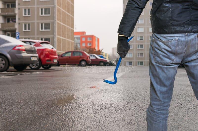 Le voleur avec le pied-de-biche va voler la voiture du parking image stock