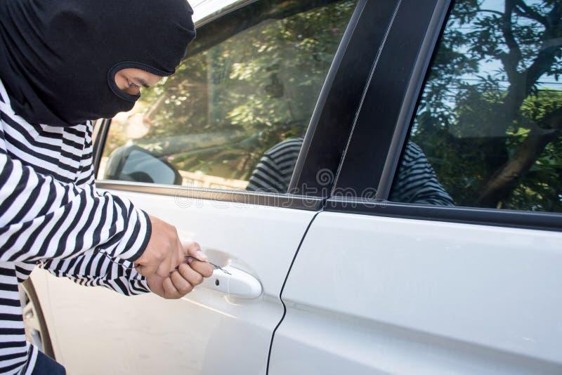 Le voleur d'homme avec un passe-montagne sur sa tête essayant de diviser en concept de voiture/voleur de criminel et de voiture images stock