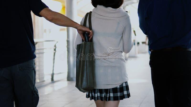 le voleur de pickpocket a pris le portefeuille de la jolie fille tout en marchant photos libres de droits