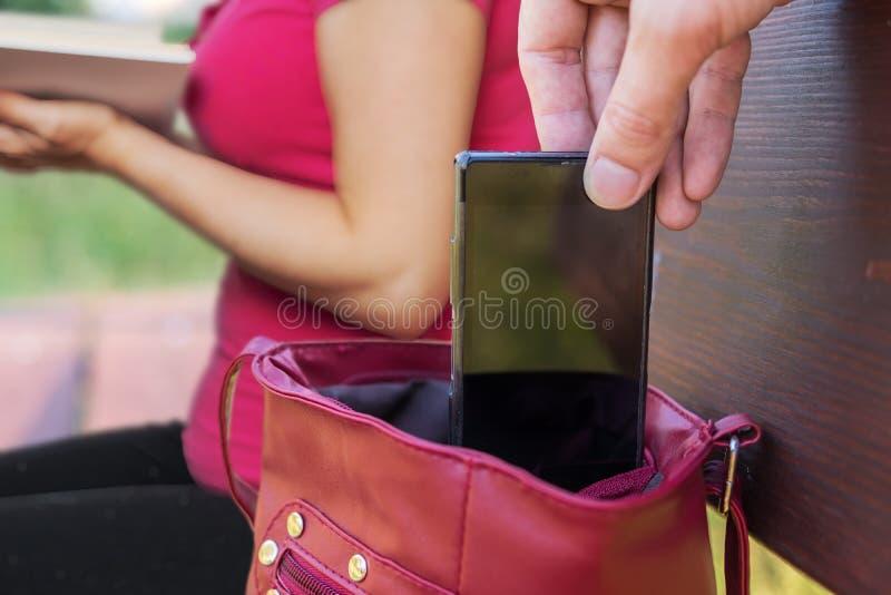 Le voleur de pickpocket vole le smartphone du sac d'un livre de lecture de femme photographie stock