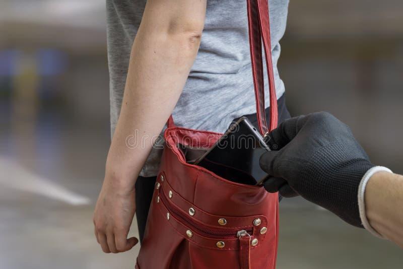 Le voleur de pickpocket vole le téléphone de la femme de son sac à main photo stock