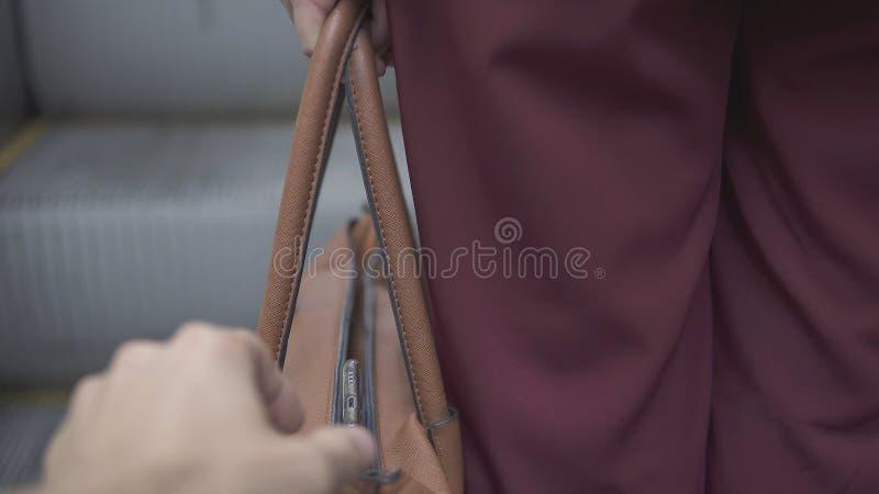 Le voleur de pickpocket vole le smartphone du sac à main orange image libre de droits