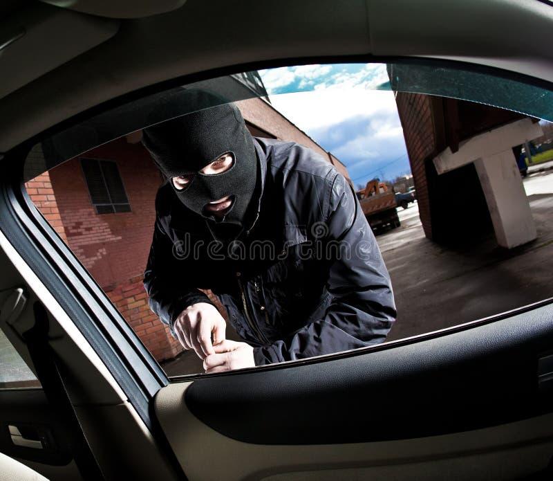 Le voleur et le voleur dans un masque détourne le véhicule photo stock